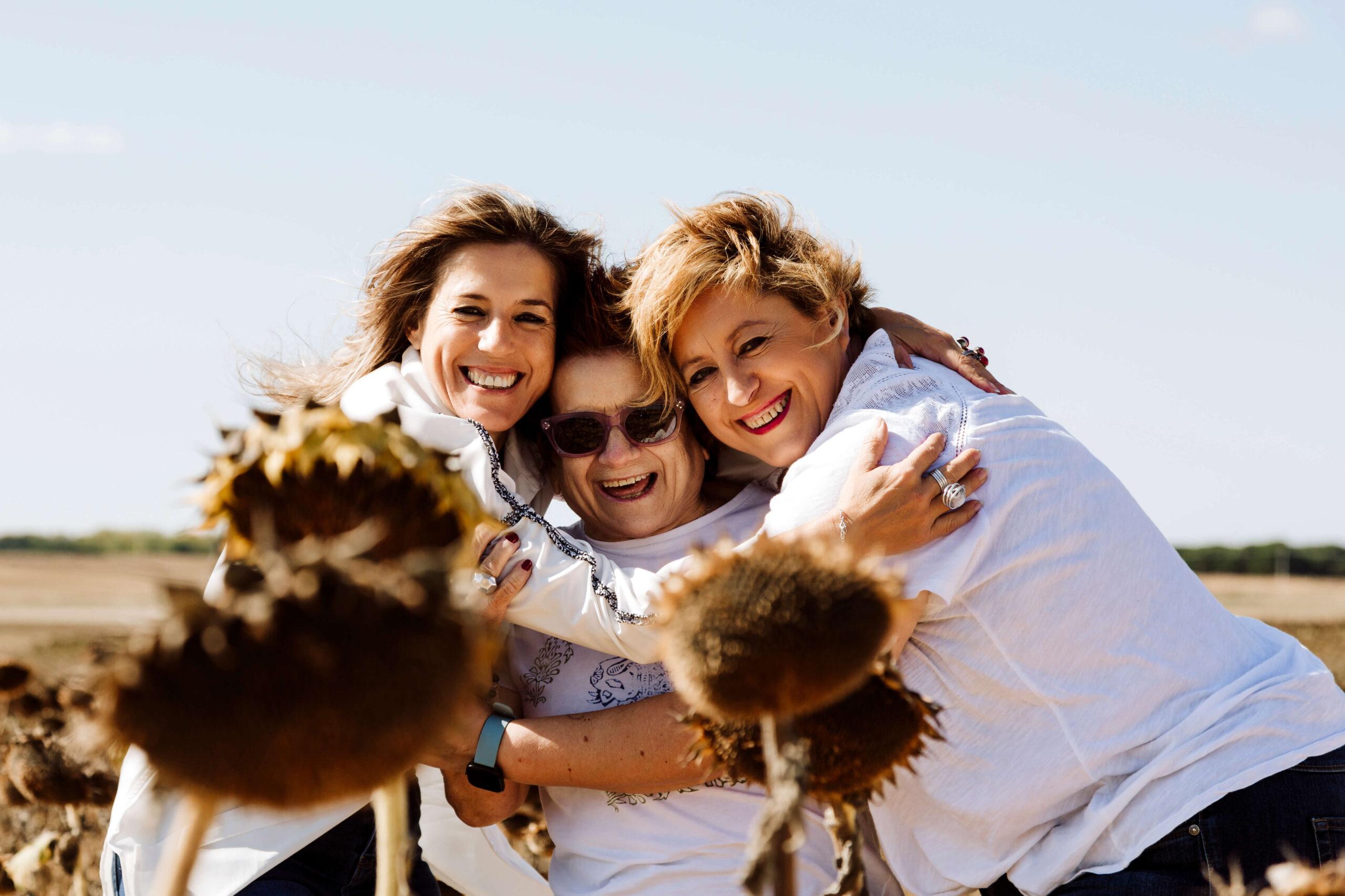 Dos hijas adultas abrazan a su madre. El viento les alborota el pelo