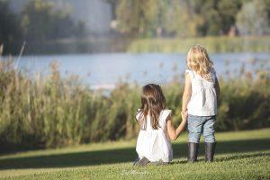 hermanas cogidas de la mano mirando al lago