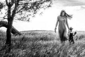 Madre de paseo por el prado con su hijo de la mano. Blanco y negro