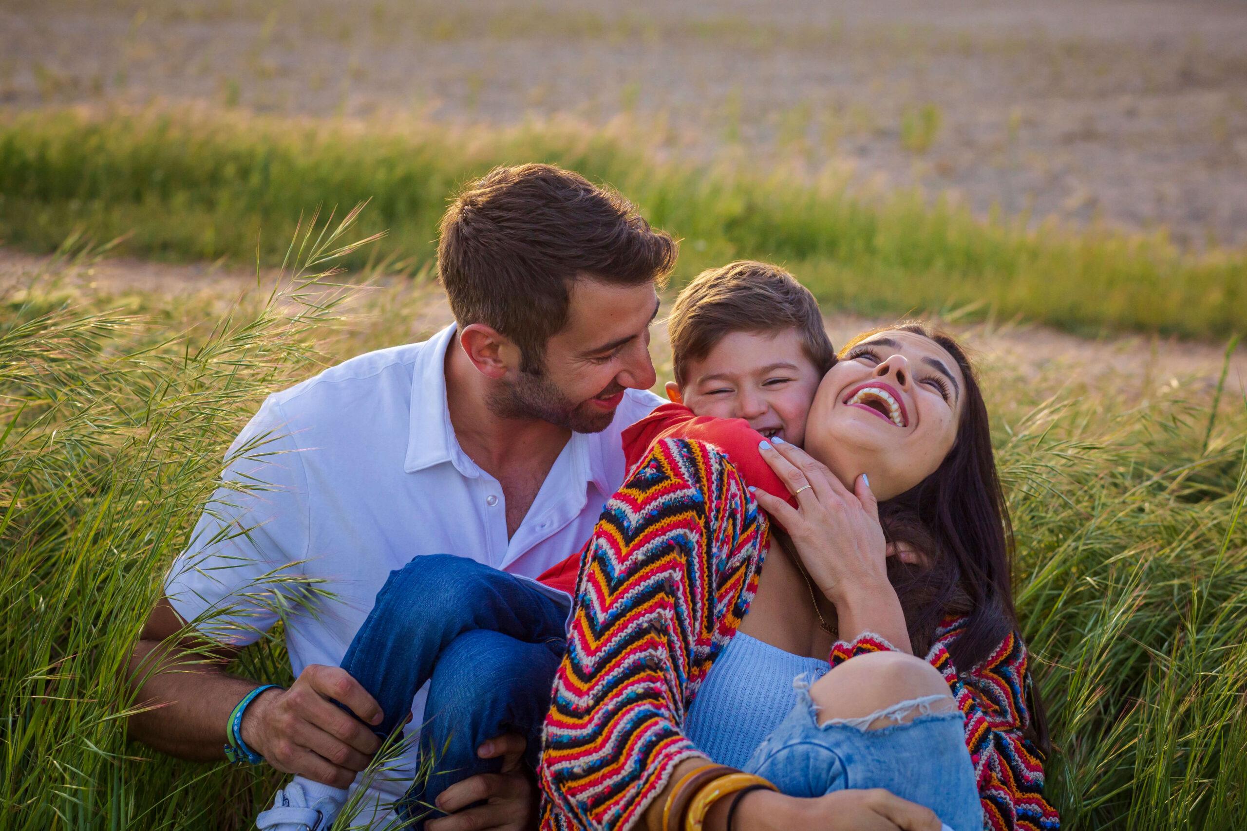 Familia posa en un prado, con el niño agarrado a los hombros de la madre mientras la hace reír