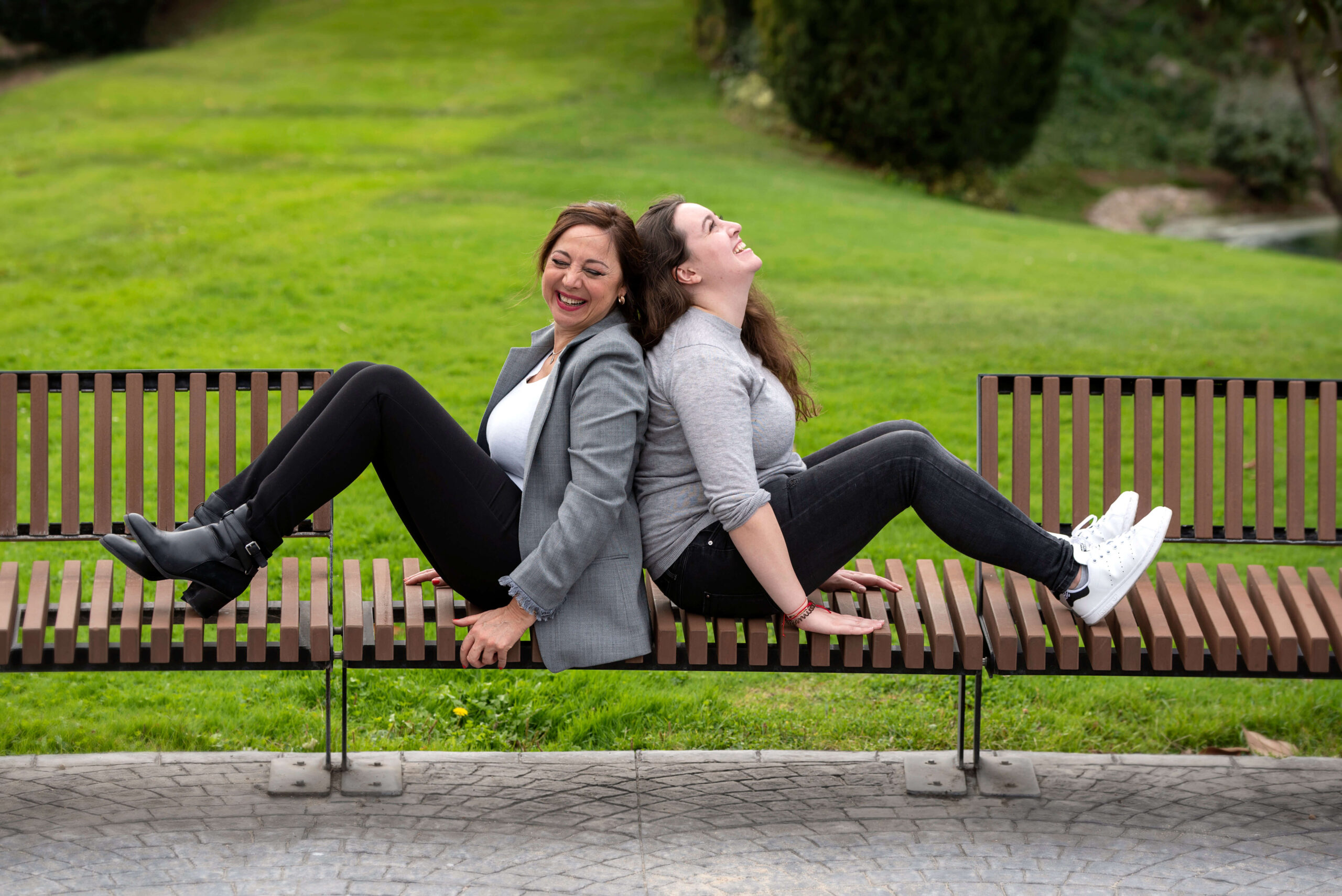 Madre e hijas ríen sentadas espalda contra espalda en un banco de un parque