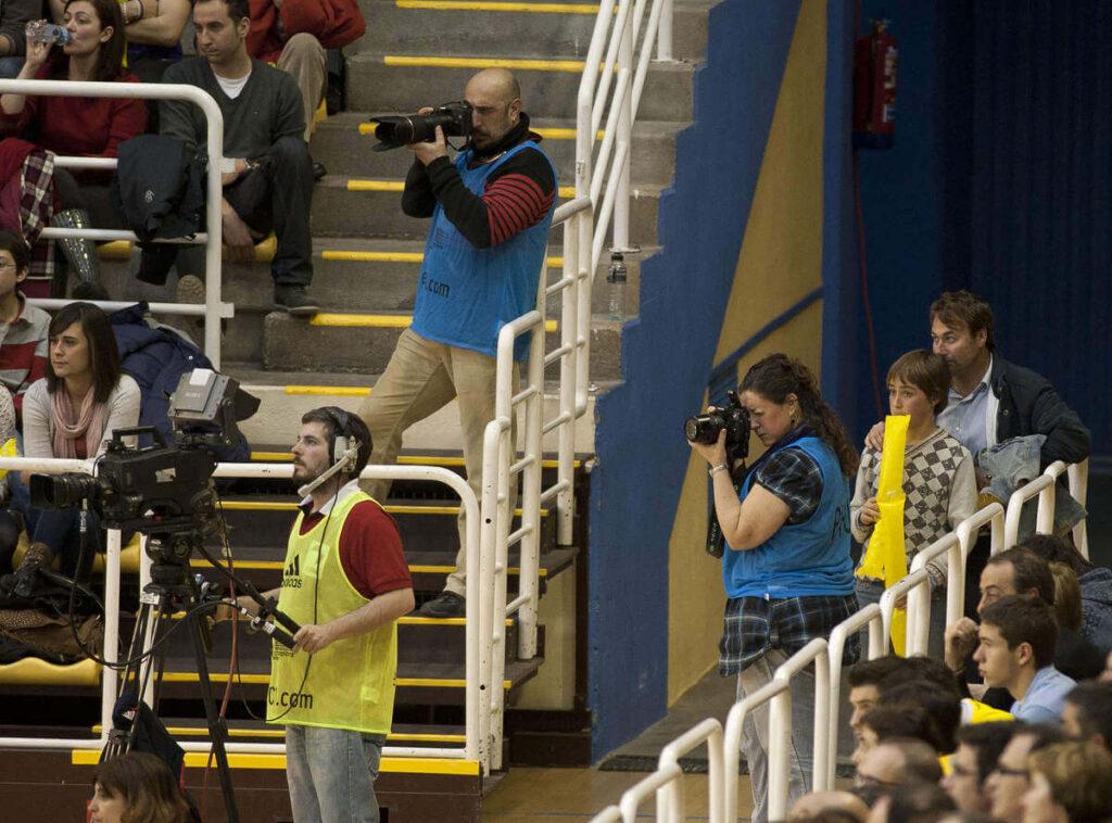 Eva Mansilla y Josetxu Moyano trabajando como fotógrafos deportivos en un pabellón
