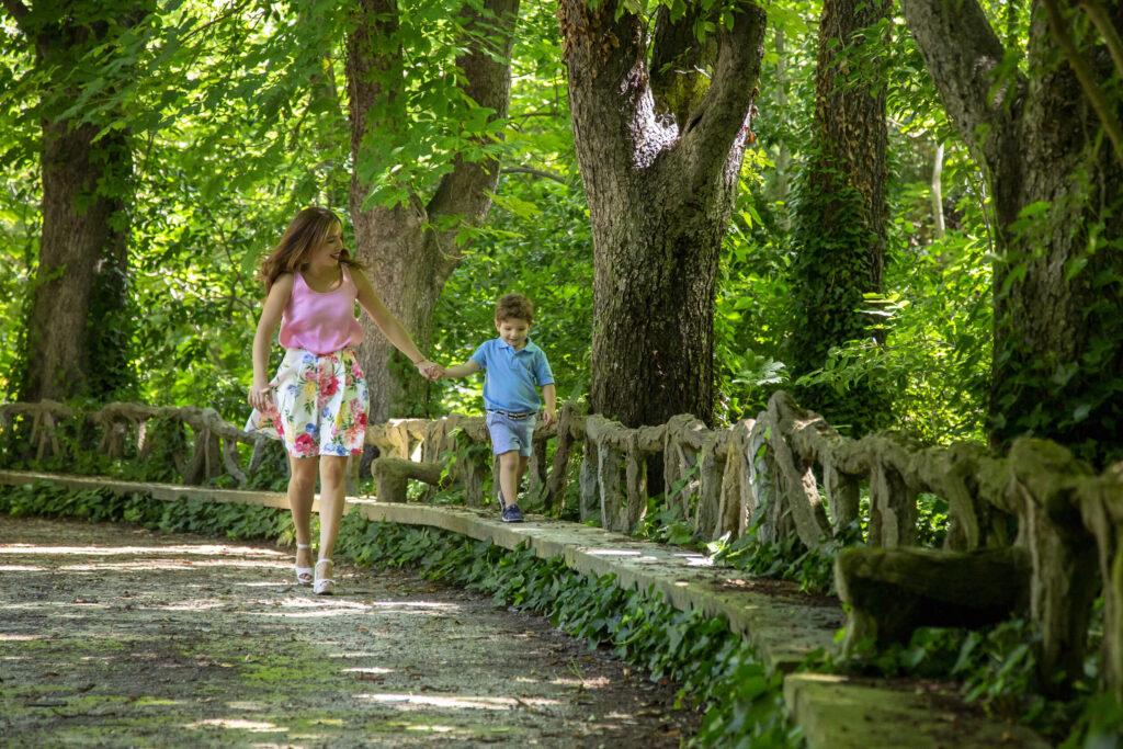 Madre paseando con su hijo de la mano por un parque