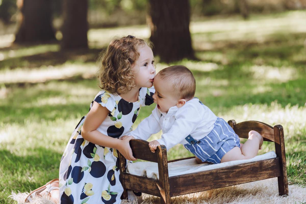 beso hermanos bebé jardín