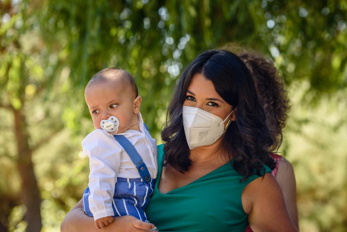 mamá con mascarilla y bebé en brazos con arboleda detrás