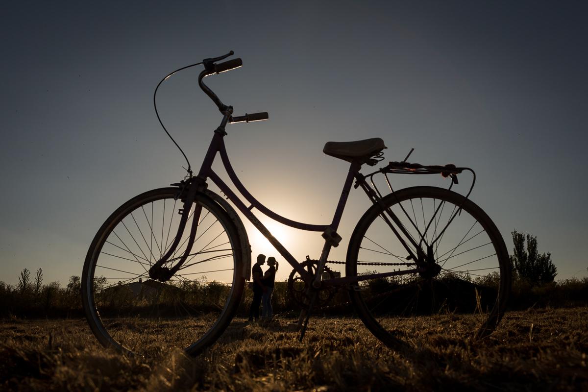 foto artística pareja novios atardecer bicicleta antigua