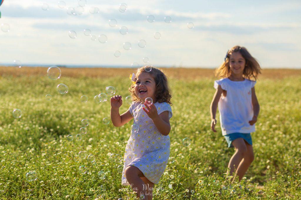 niña jugando entre margaritas nubes y pompas de jabon