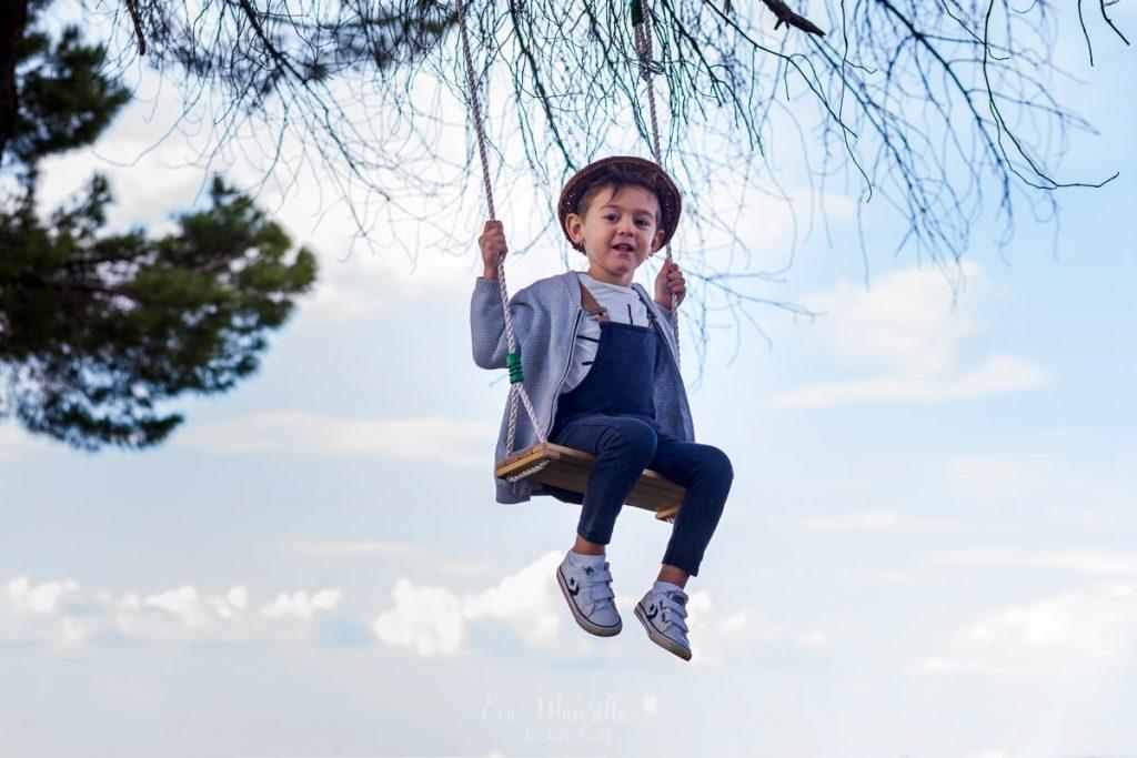 niño columpio entre árboles y nubes