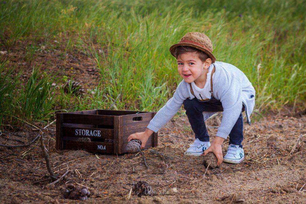 niño recogiendo piñas en el pinar