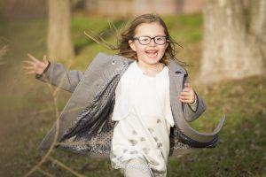 niña corriendo por el parque con abrigo de paño gris